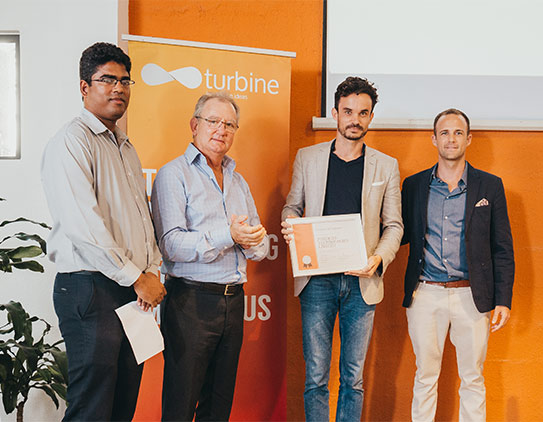 Hector Noel presenting the Fundkiss Technologies Limited team with their graduation certificate for the Turbine Incubation Program.